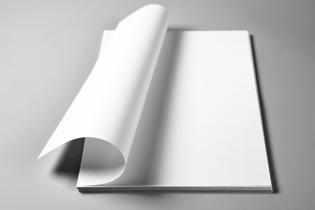Heap of blank sheets of paper with curled upper page Stock Photo