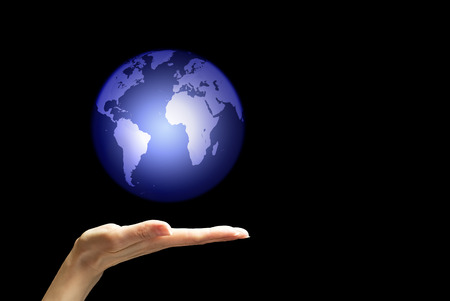 Hand catching or throwing up globe isolated over black background Stock Photo