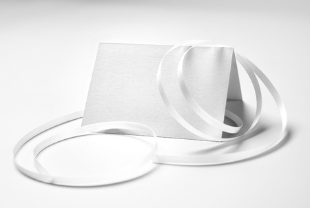 Blank greeting card with ribbon over gray background
