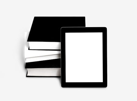 Blank tablet or e-book and pile of old books