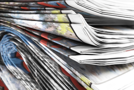 Stack of old folded newspapers, selective focus