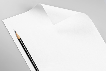 Blank sheet of paper with curled corner and pencil, over gray backgroundBlank sheet of paper with curled corner and pencil, over gray background