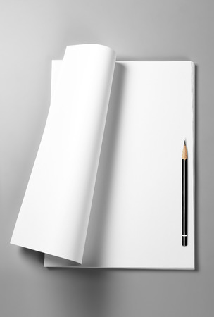 Pile of blank sheets of paper with curled upper page and pencil