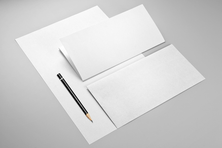 Blank sheet of paper, folded sheet of paper, envelope, and pencil