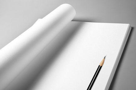 Heap of blank sheets of paper with curled upper page and pencil Stock Photo