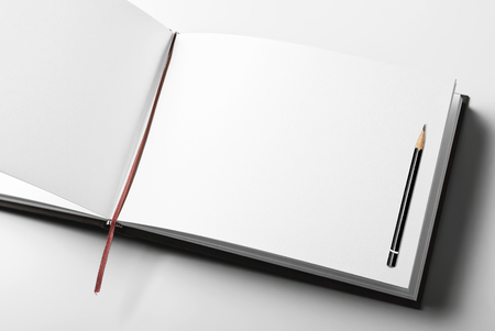 Blank open diary or sketching book with pencil