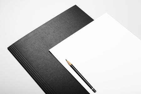 Blank sheets of paper and pencil over black folder