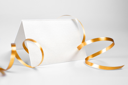Blank folded thank you or greeting card decorated with gold ribbon Stock Photo