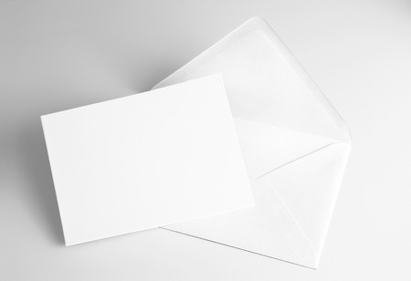 Blank white card and envelope over grey background