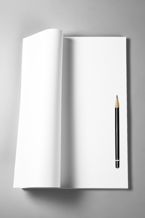 Open blank book, magazine, diary, or sketching book with curled upper page and pencil Stock Photo