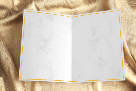 Blank open greeting card with yellow frame over gold draped fabric Stock Photo