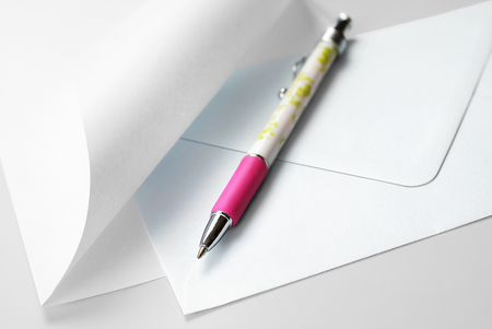 Correspondence Set: Blank Sheet of Paper with Curled Corner, Envelope and Pen Stock Photo