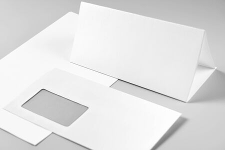 Blank Folded Sheet of Paper, Letterhead or Flyer, and Envelope over Stack of Paper
