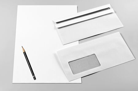 Two Envelopes, Blank Sheets of Paper, and Pencil over Grey Background Standard-Bild