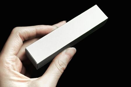Female hand holding blank box or cosmetic package
