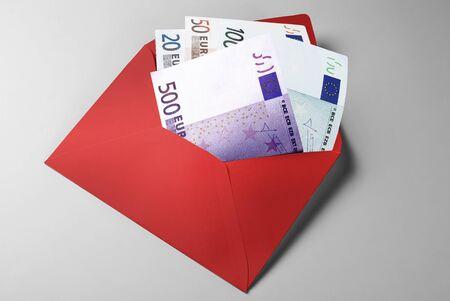 Financial aid: 20, 50, 100, and 500 Euro Bills in red envelope Standard-Bild