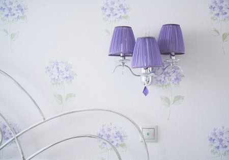 Lilac lamp, switch and a fragment of a bed beck in a llight bedroom with flowered wallpaper
