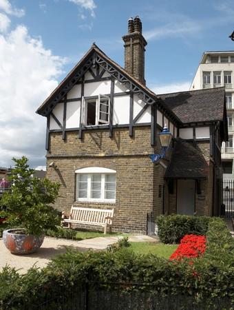 Het kleine huis met wit bankje Stockfoto