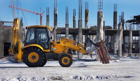 Winter bouwplaats met een graafmachine en kraan Stockfoto