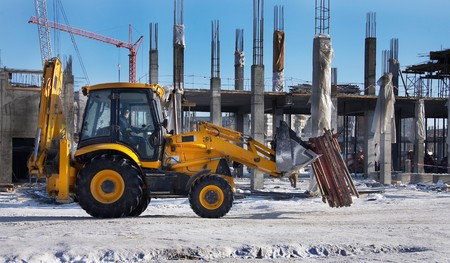 loaders: Winter construction site with excavator and crane