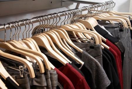 Modern women clothes on wooden hangers Standard-Bild
