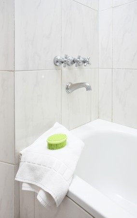 Green massage brush on white double towel in modern bathroom Standard-Bild