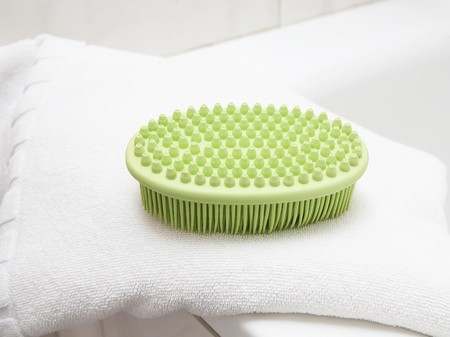 Green massage brush on white double towel
