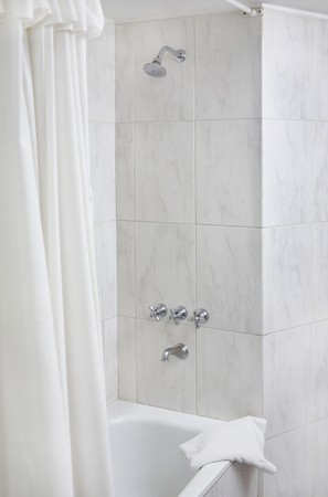Modern bathroom corner with shower, taps, towel and other details photo