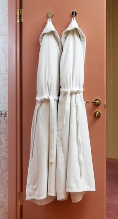 Modern bathroom door with two white bathrobes