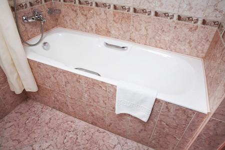 Het deel van een bad kamer met bad, tik, hand doek en andere details