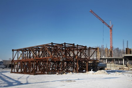 steel beam: Winter construction site with iron frames and crane Stock Photo