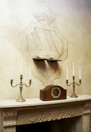 Mantelshelf with clock and burned candles in candelabrums and some emblem with crown on a texture wall photo