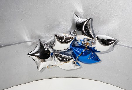 blown: Six star silver and blue balloons with golden ribbons under ceiling Stock Photo