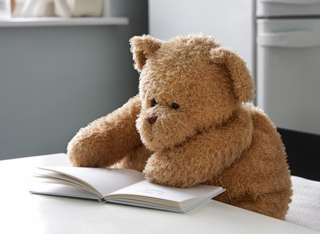 play time: Teddy bear reads a book Stock Photo