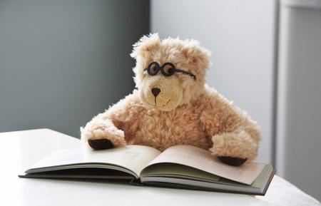 Teddy beer in glazen leest een boek Stockfoto