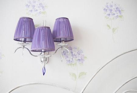 Lilac lamp and a fragment of a bed beck in a llight bedroom with flowered wallpaper Standard-Bild