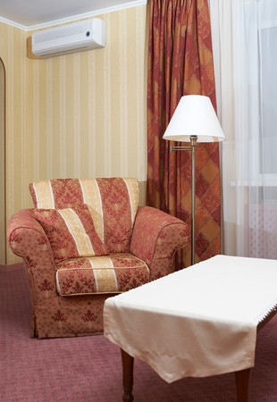 Cenral part of a modern drawing-room with an armchair, lamp and small table photo