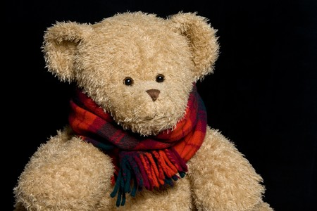 sweetness: Teddy bear in scarf close up portrait on black background Stock Photo