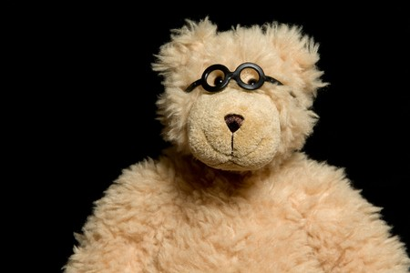 playthings: Teddy bear in glasses close up portrait on black background Stock Photo