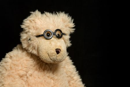 sweetness: Teddy bear in glasses close up portrait on black background Stock Photo