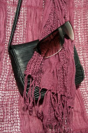 Small black bag, sunglasses and rose viscose scarf Stock Photo