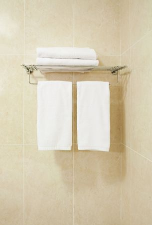 Modern bathroom part with four white bath towels Ð straight view photo