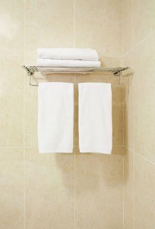 Modern bathroom part with four white bath towels Ð straight view