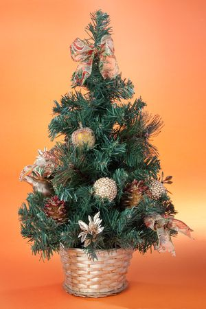 Small Christmas tree decoration in gold basket onorange background photo