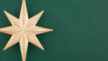 compliment: Part of Christmas decoration gold star on green textured paper background. Useful for any type of Christmas card Stock Photo