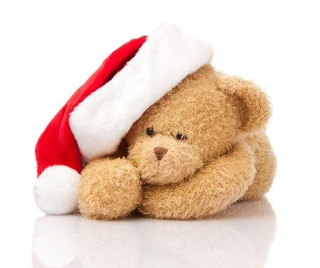 Christmas teddy bear in Santa cap laying on white photo