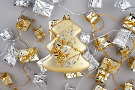 Christmas decoration gold tree with garland from silver and gold gift boxes on gray background photo