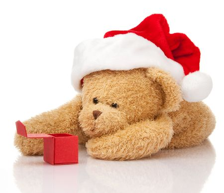 Christmas teddy bear in Santa cap with gift box laying on white photo