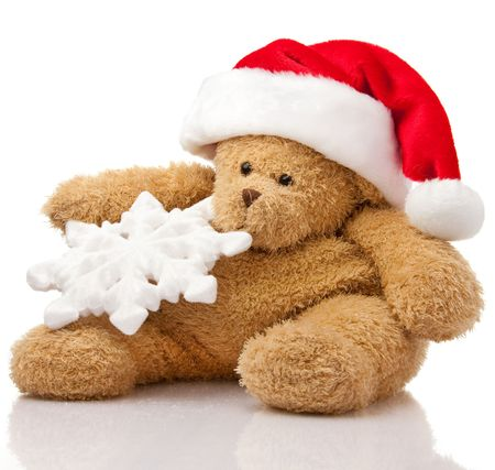 Christmas teddy bear in Santa cap with snowflake sitting on white photo