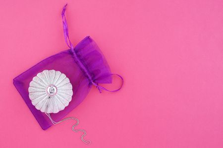 Christmas decoration silver ball with silver chain and lilac bag on pink background with empty place for your text photo